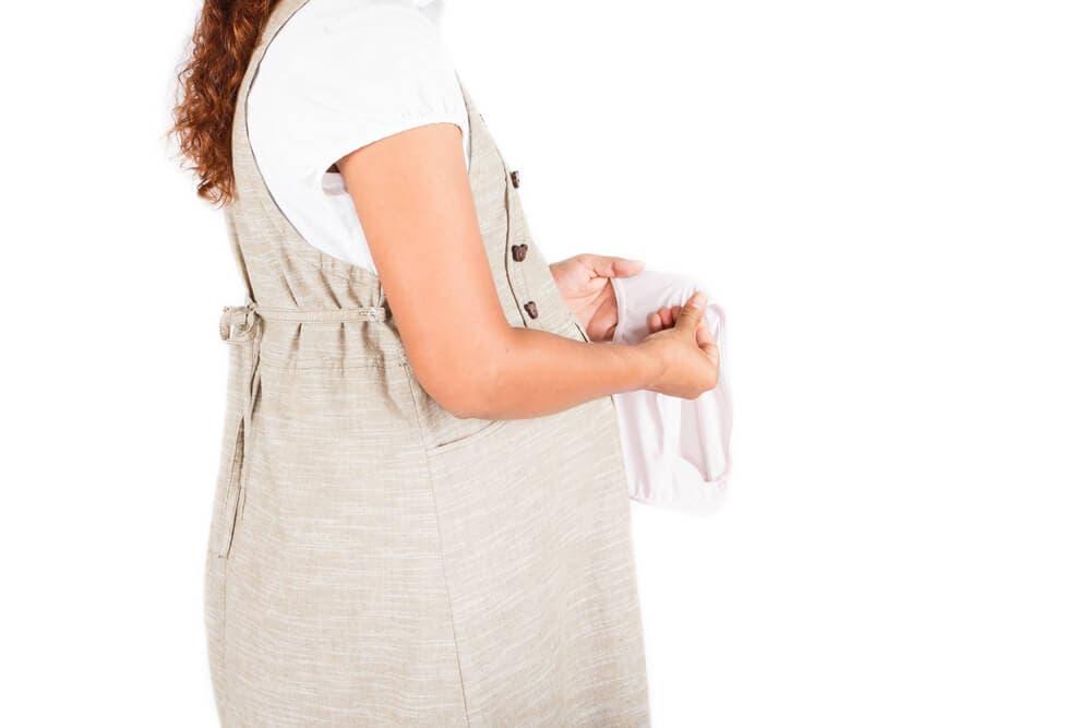 elindeki iç çamaşırına bakan bir hamile