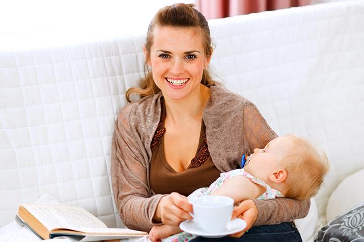 Çay içen ve yanında bebeği olan bir kadın
