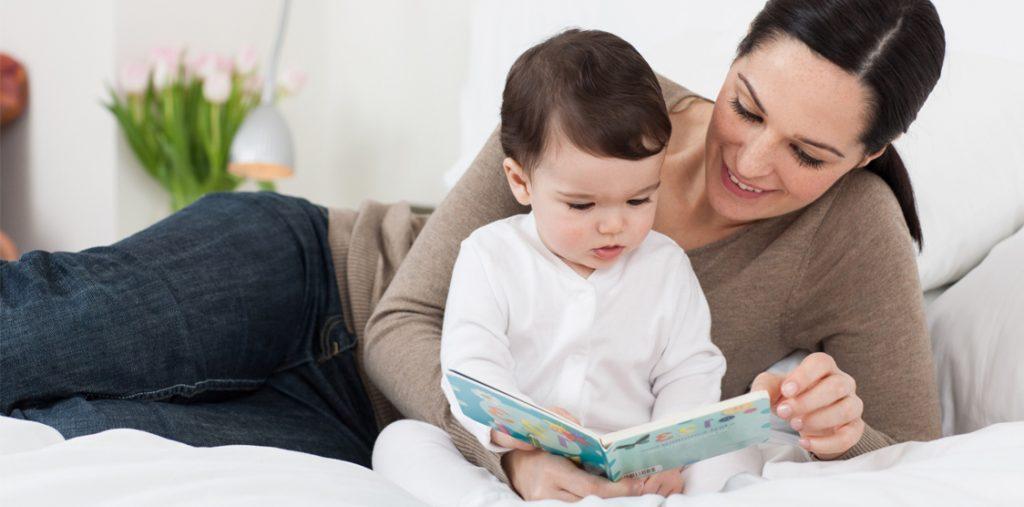 bebeğine kitap okuyan anne