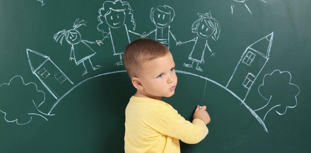 kara tahtaya çocuk, ev, ağaç gibi şekiller çizen bir erkek çocuk