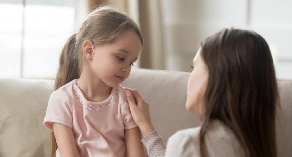 bir anne küçük kızını teselli ediyor