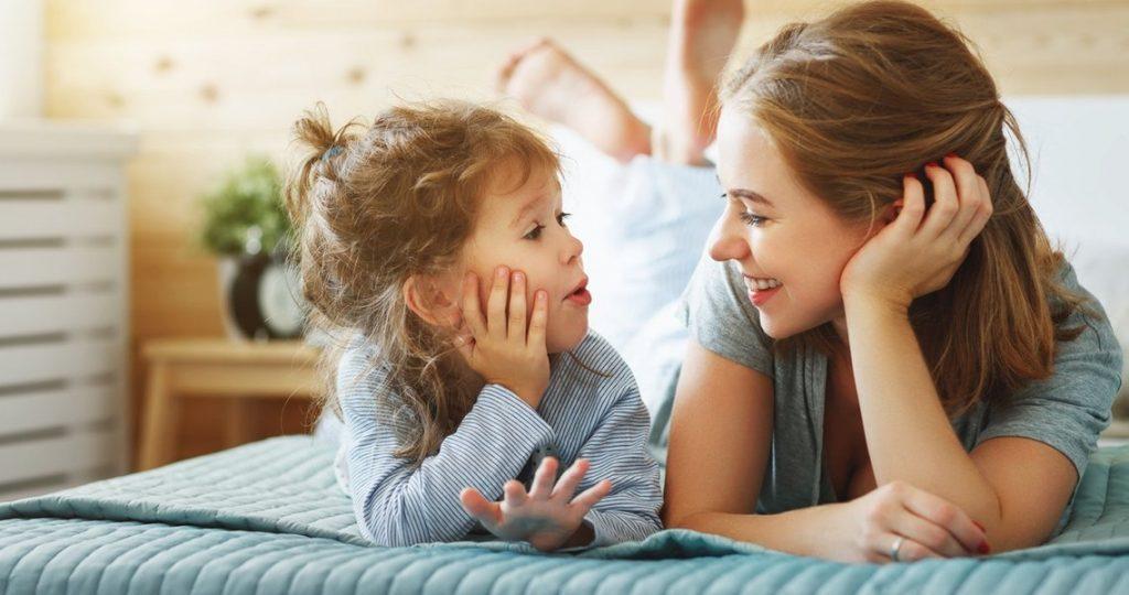 Küçük kız çocuğu heyecanlı bir şekilde annesiyle sohbet ediyor
