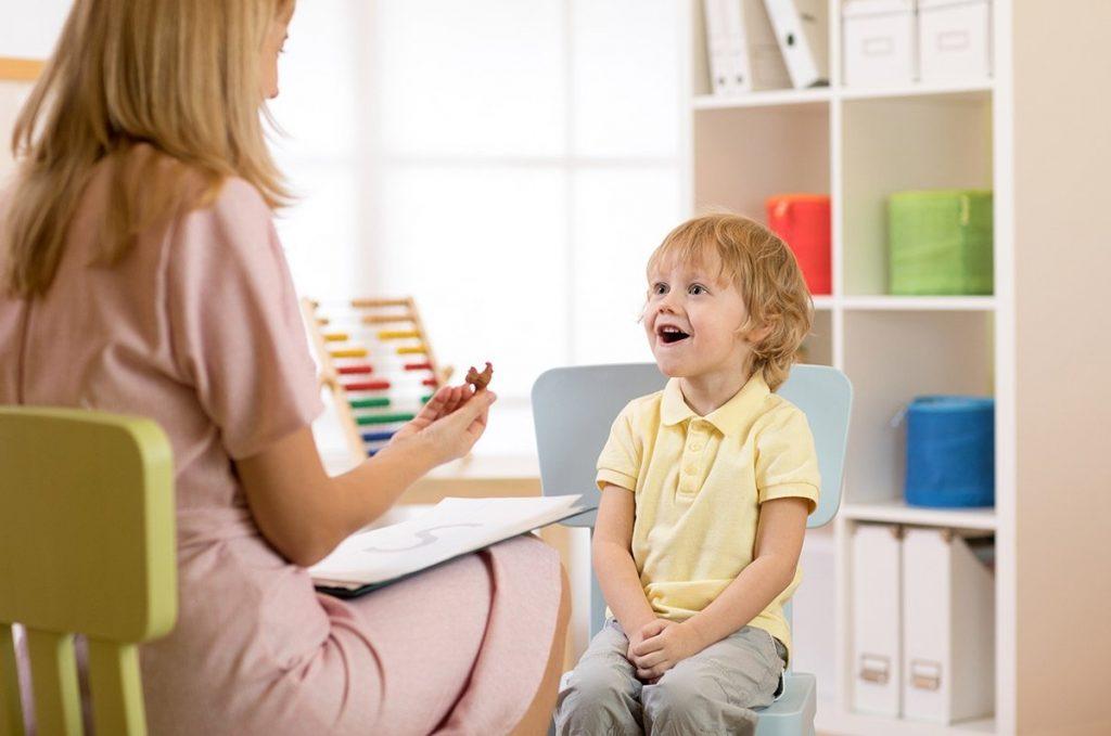 Öğretmeniyle karşılık oturan şaşkın küçük bir çocuk