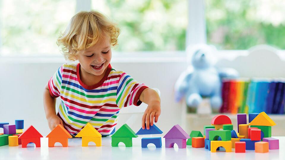 Lego oyuncaklardan çok sayıda ev yapan bir çocuk