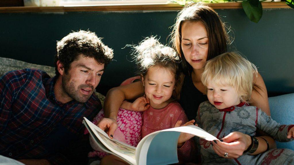 anne ve baba iki çocuğuna kitap okuyor