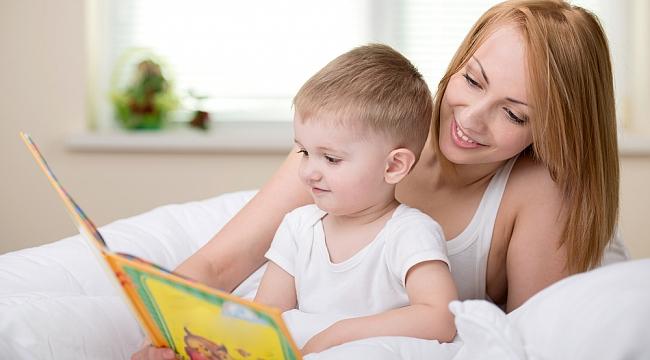 Bebeğine kitap okuyan bir anne