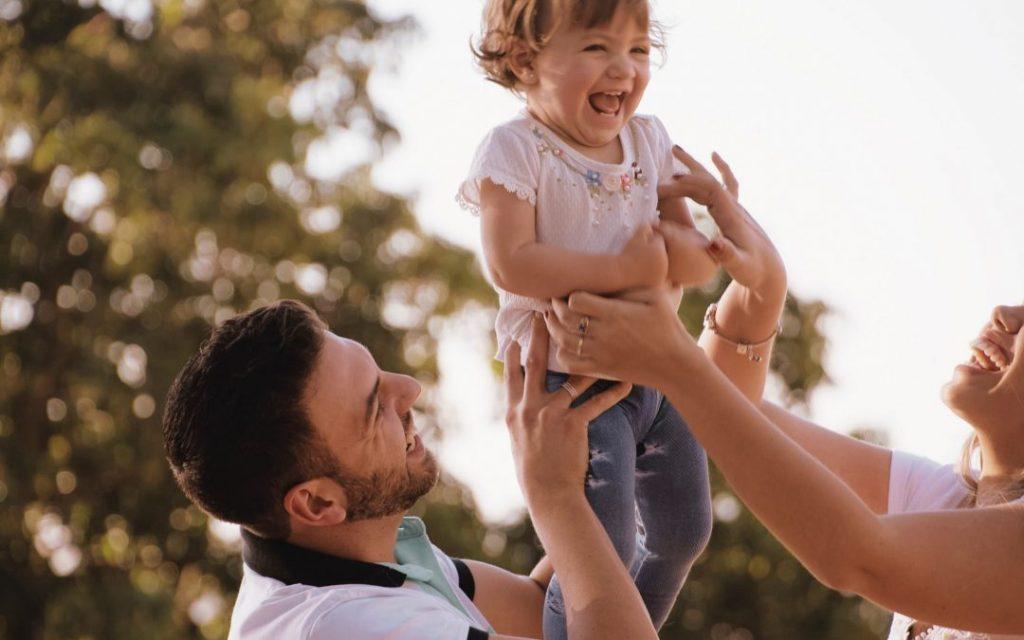 anne ve baba bebeklerini havaya kaldırmış gıdıklıyorlar