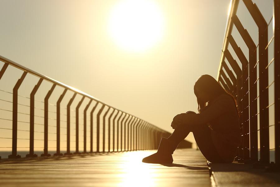 Genç bir kız iskelede üzgün bir halde oturuyor