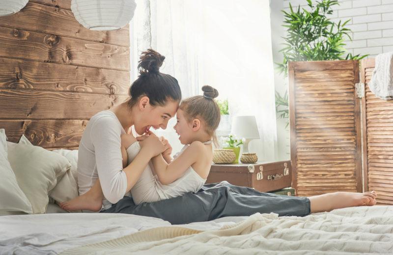 bir anne ve kızını yatakta kucaklamış birbirlerine bakarak gülüyorlar