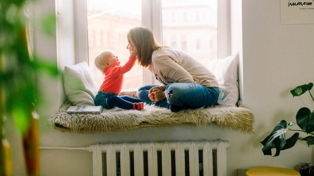 bir anne ve bebeği cam kenarında birbirlerine bakıp gülüyorlar