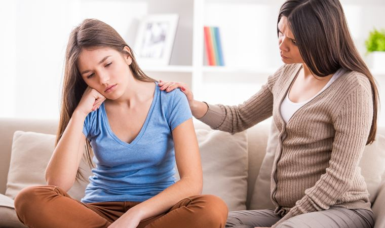 Bir anne üzgün kızıyla konuşmaya çalışıyor