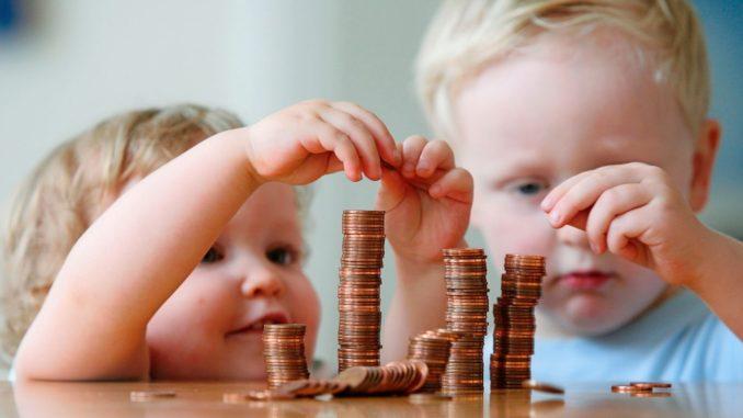 bozuk paraları üst üste dizmeye çalışan iki erkek çocuk