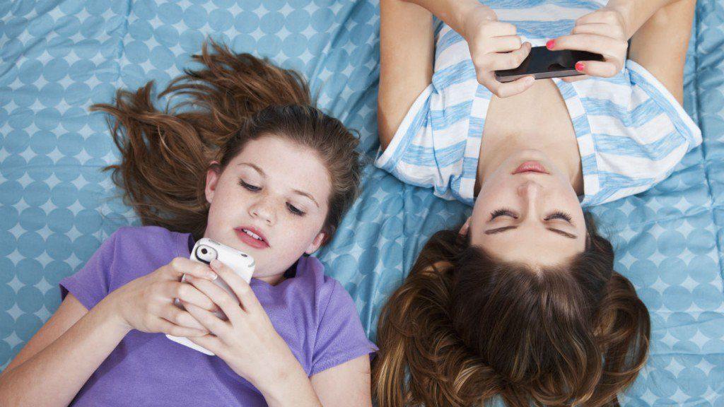 iki genç kız yatakta yan yana uzanırken mesajlaşıyorlar